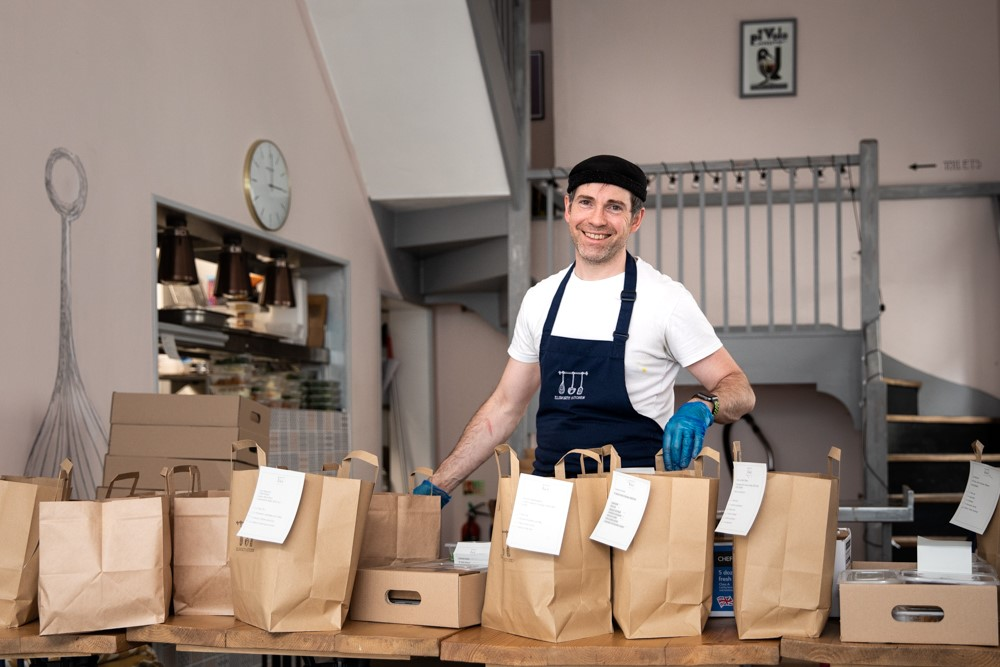 Chef-Owner Bruce Elsworth stands with meals freshly cooked and ready for home delivery