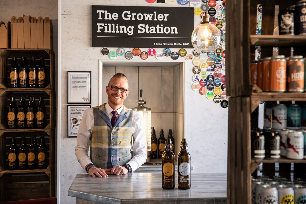 Artisan beer shop owner stands at the counter in his Skipton shop, The Growling Shrew