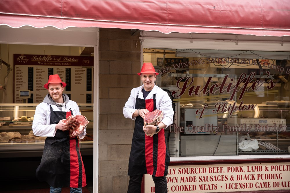 Butchers of Sutcliffe's in Skipton stand outside their shop with fresh cuts of meat in their hands.